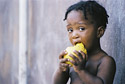 Young Haitian boy eating a mango